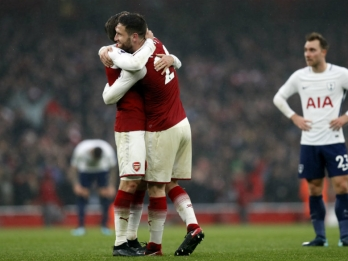Arsenal overwhelms Tottenham, Man City keeps up title charge